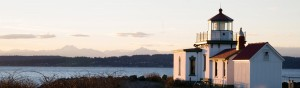 A Washington State lighthouse along the Puget Sound as the sun sets over the Olympic Mountains