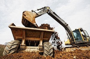 A large digger loads dirt into a waiting dump truck