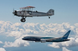 Two planes fly in formation, one a biplane, the other a modern jet