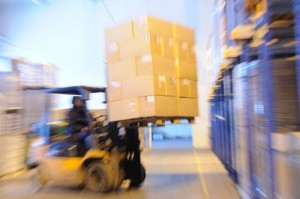 A forklift lifts a pallet of product onto a warehouse shelf