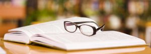 A pair of glasses rest on a book in a library