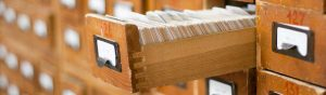 A single drawer of a library card catalog remains open