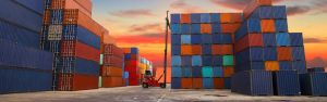 A forklift stacks containers on a dock as the sun rises