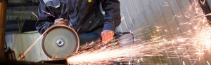 An operator works a hand grinder on a piece of metal, sending off a shower of sparks