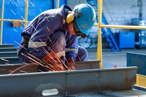 A worker welds two plates together in a drydock