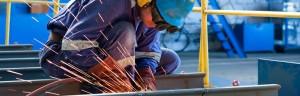 A welder mends a steel plate in a dockyard