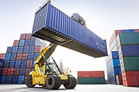A forklift carries an empty cargo container on a dock
