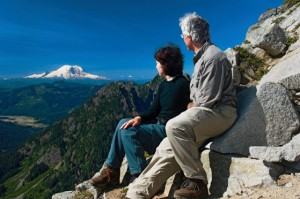 A couple enjoys their view of Mount Rainier from a rock outcropping