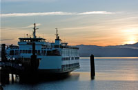 A Washington State ferry departs a dock as the sun sets over Puget Sound