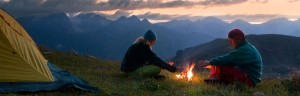 A couple camping huddle around a campfire in the Olympic Mountain range