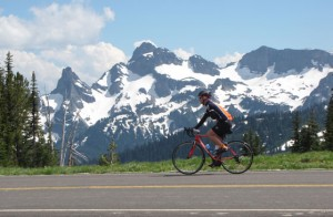 A bicyclist coasts down a mountain roadway with Mount Rainier behind him
