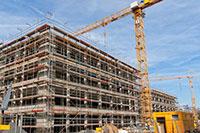 A crane lifts some construction materials onto a building under construction