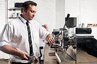 A man brews espresso behind a counter