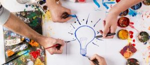 Four artists paint a light bulb on a piece of paper