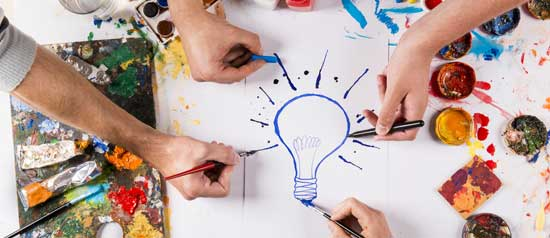 Four people draw a light bulb on a piece of paper with markers and paints.