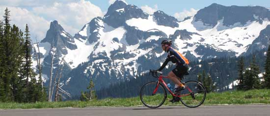 A bicyclist coasts down a mountain slope with Mount Rainier in the background.