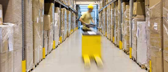 A forklift driver speeds down a warehouse aisle to retrieve an order.