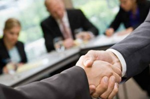 Two businessman shake hands at a meeting