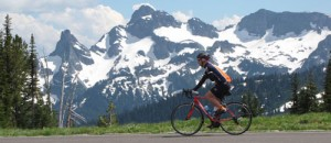 A bicyclist races past Mount Rainier on his bicycle
