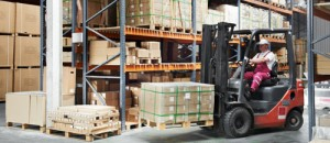 A forklift carries a pallet of goods in a fulfillment warehouse