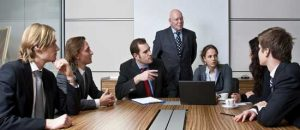 A team of experts discuss a problem in a meeting room