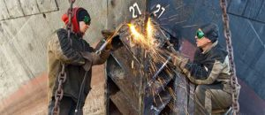 Maritime workers weld a bow plate into place