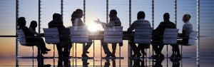 Employees sit around a conference table, backlit by a setting sun in the glass window