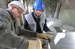 A worker shows another worker how to clamp two pieces of metal together
