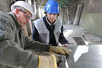A supervisor trains a journeyman machinist on a process