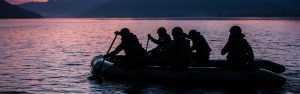 Military SEALS paddle an inflatable past a Washington State island on maneuvers.