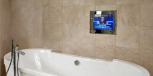 A bathroom with a television behind a mirror, built by Electric Mirror in Everett, Washington