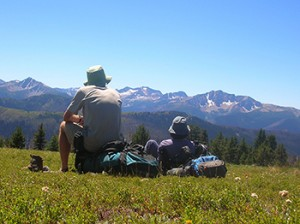 Two hikers enjoy the view while on a hike in the Cascades