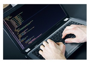 A programmer reviews computer code on a laptop