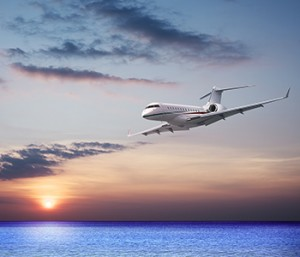 A Gulfstream jet flies low over the water on approach to an airport