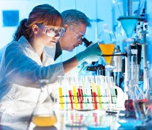 Two scientists work in a lab with a microscope and test tubes