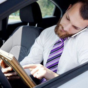 A guy on his computer tablet and phone checks his messages in a car