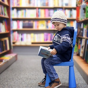A small child reads a book, seated in a bookstore aisle