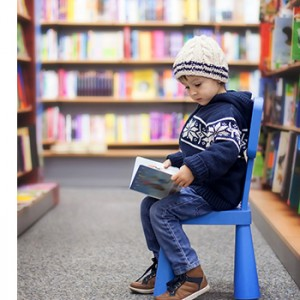A child sits in a bookstore aisle reading a book