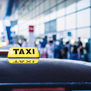A taxi waits outside an airport