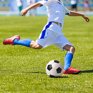 A soccer player connects with a soccer ball on the field