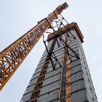 A construction crane next to a highrise under construction in downtown Seattle.