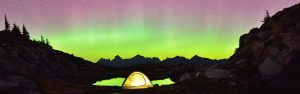 Campers in a tent enjoy the view in the Cascades of the Northern Lights on a clear night
