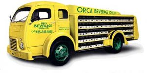 A yellow and green Orca Beverage truck that is being restored
