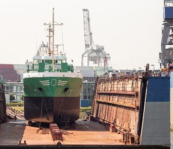 A large vessel rests in a drydock, awaiting repairs