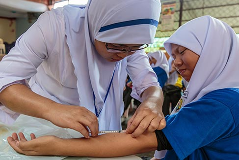 A nurse immunizes a child in a small community clinic.