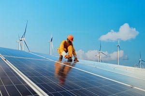 A worker installs solar panels in a field.