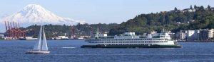 A ferry passes West Seattle with Mount Rainier in the background.