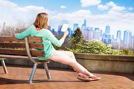 A woman sits on a park bench, reading a book with the Seattle skyline in the background