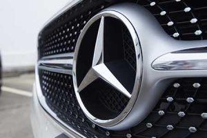 The Mercedes-Benz logo adorns the front of a new car.
