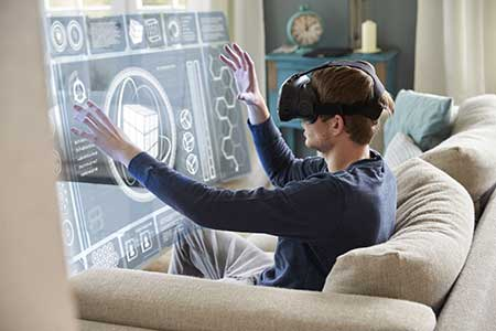 A man on a sofa interacts with a virtual screen using virtual reality goggles.
